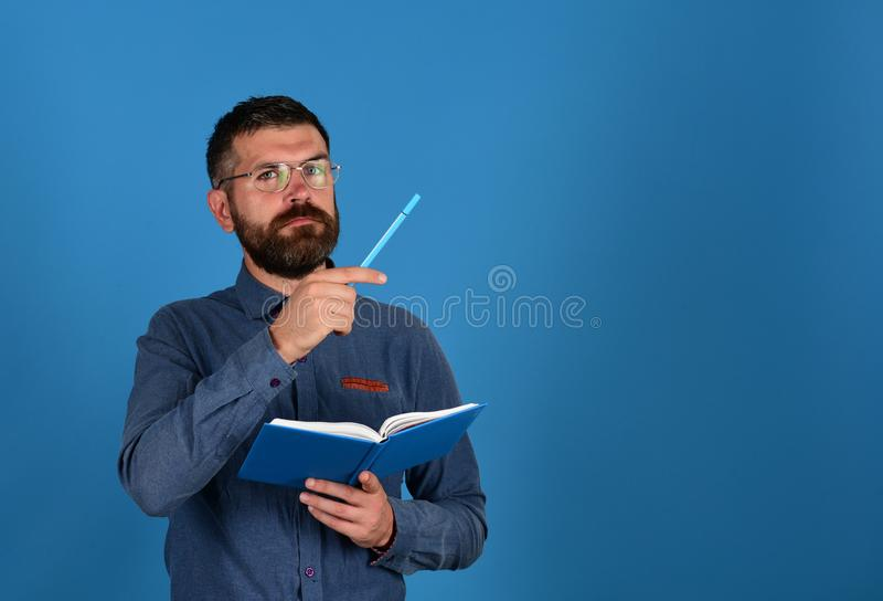 Man with beard and glasses holds book and marker royalty free stock photo