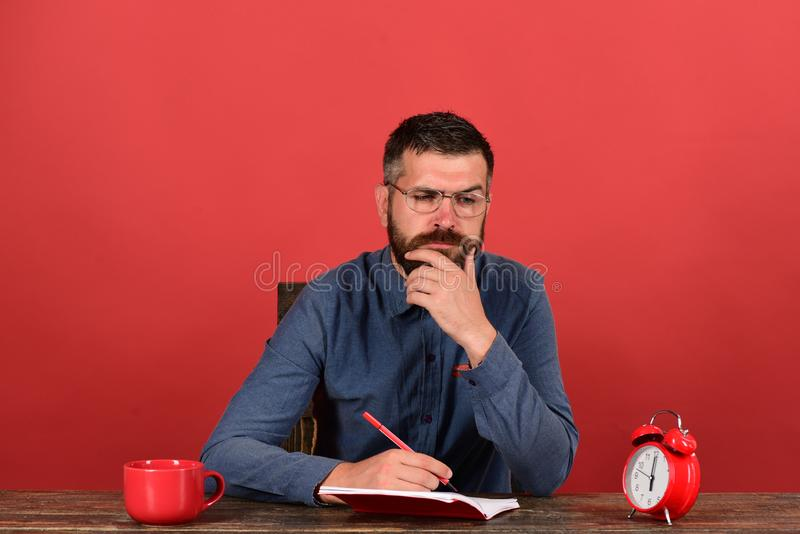 Man with beard, glasses writes in notebook on red background stock photography