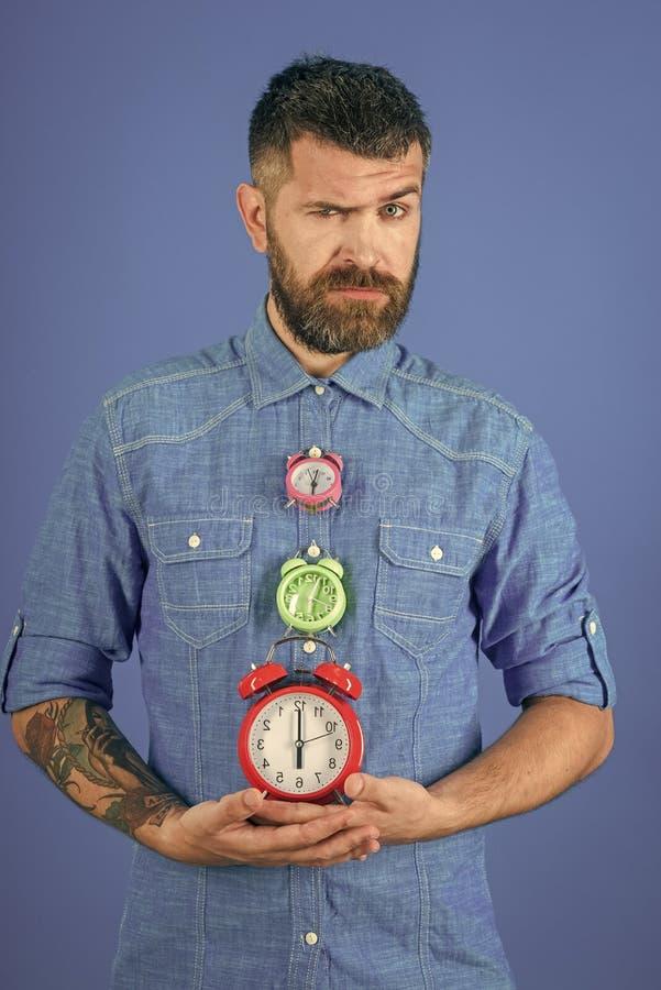 Man with beard hold alarm clock. stock photo