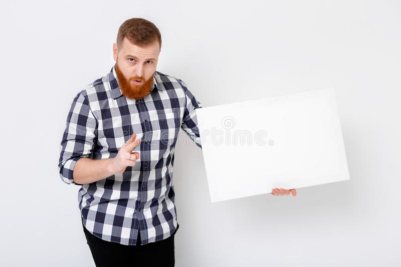 Man with beard holding big white card. royalty free stock image