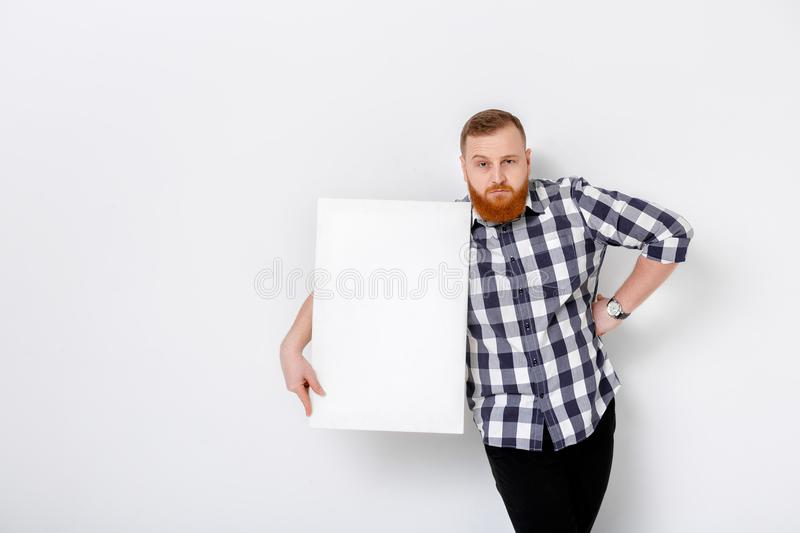 Man with beard holding big white card. royalty free stock photo