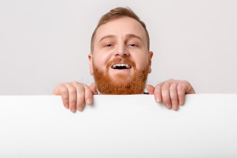 Man with beard holding big white card. stock photos