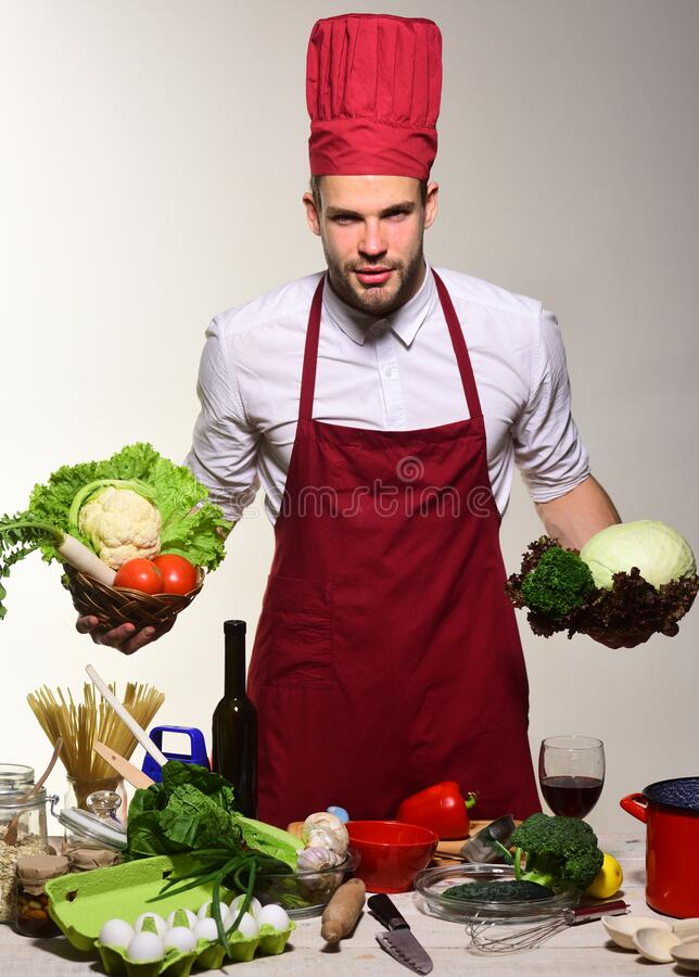 Man with beard holds cabbage and lettuce on grey background. stock images