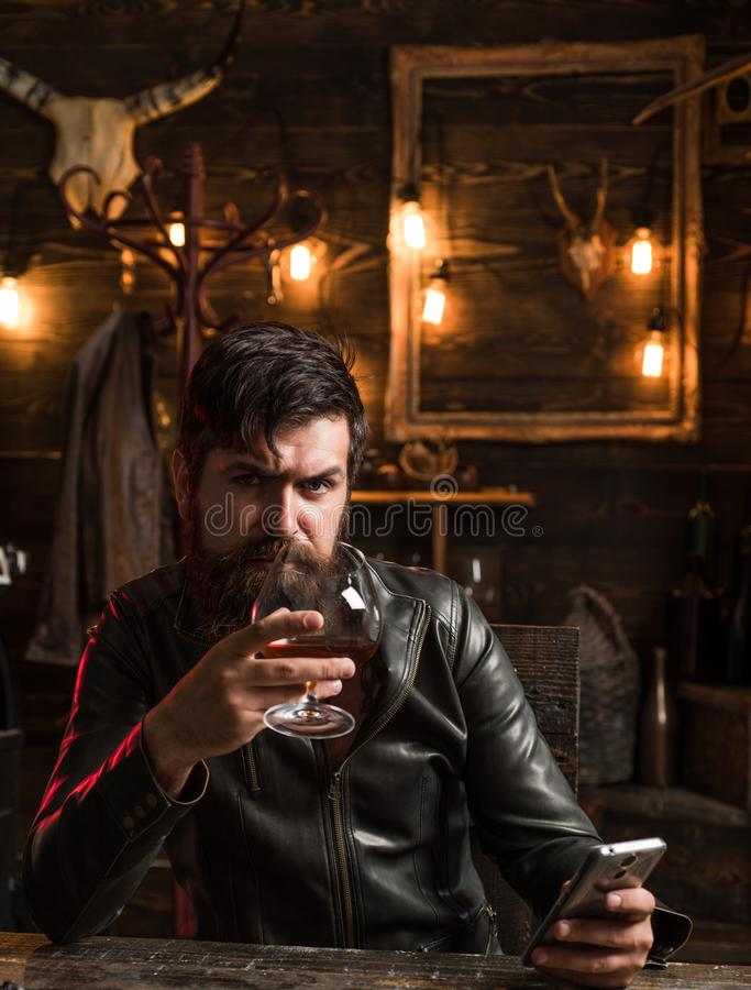 Man with beard holds glass brandy. Macho drinking. Degustation, tasting. Handsome stylish bearded man is drinking. Whiskey royalty free stock photos