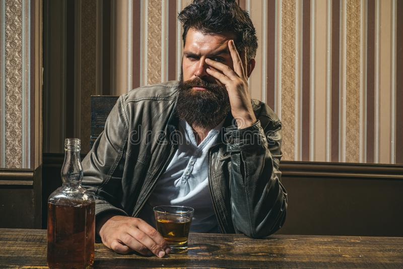 Man with beard holds glass brandy. Man holding a glass of whisky. Handsome stylish bearded man is drinking at home after royalty free stock photography