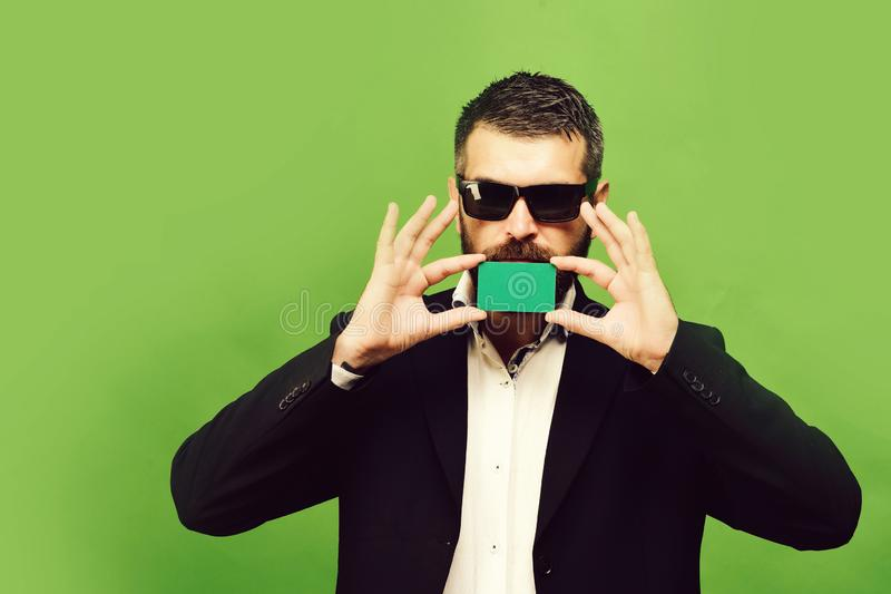 Man with beard holds green business card near mouth. Businessman with empty card, copy space. Business and success concept. Guy with serious face and royalty free stock photography