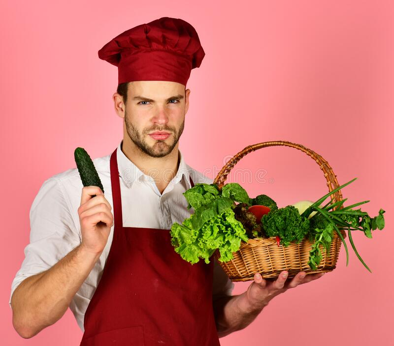 Man with beard holds vegetables on pink background. Culinary concept. stock image