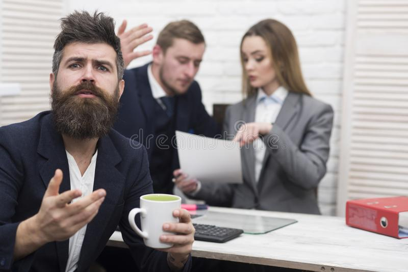 Man with beard on hopeful face holds mug, bosses, coworkers, colleagues on background. Business negotiations concept stock image