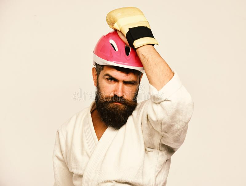 Man with beard in kimono and pink helmet on white. Background. Combat master celebrates gets ready to fight. Karate man with serious face in boxing gloves puts stock images