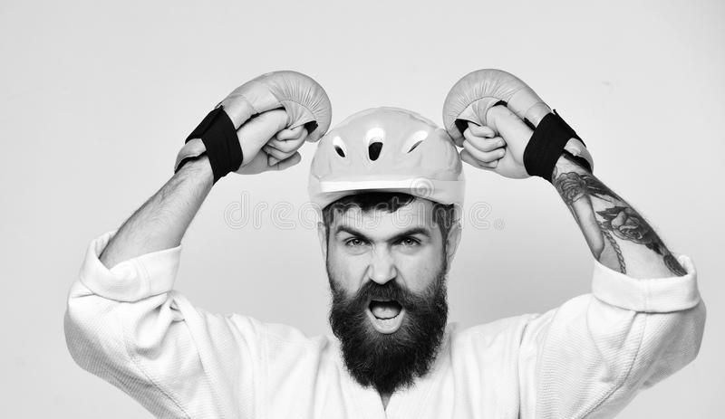 Man with beard in kimono and pink helmet on white. Background. Karate man with yelling face in boxing gloves puts safety helmet on. Workout and boxing concept royalty free stock photography