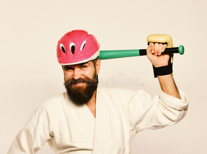 Man with beard in kimono and pink helmet on white background. MMA sports concept. Combat master gets ready to fight royalty free stock images