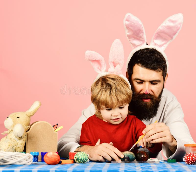 Man with beard and little boy painting eggs for Easter. On pink background. Father and son preparing for holiday. Easter celebration and joy concept. Dad with stock photo