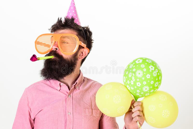 Man with beard and mustache on calm face holds air balloons, white background. Guy in party hat with party horn. Celebrates. Party concept. Hipster in giant royalty free stock photo