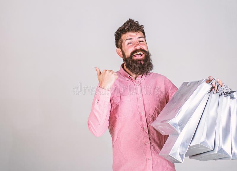Man with beard and mustache carries bunch of shopping bags, grey background. Guy shopping on sales season, pointing at. Blank surface. Recommendation concept royalty free stock photography