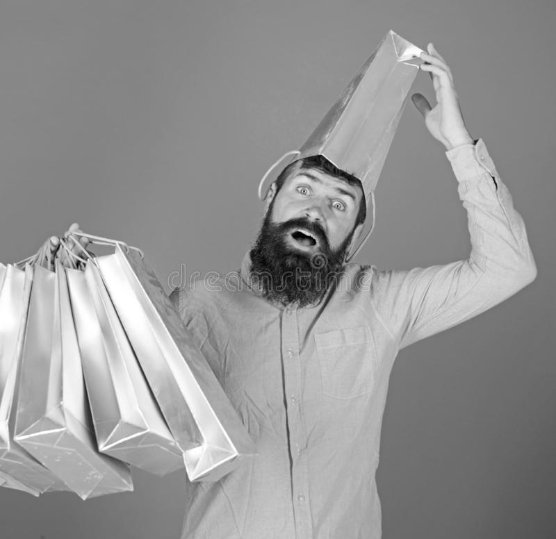 Man with beard and mustache carries shopping bags, blue background. Shopping concept. Guy shopping on sales season with. Discounts. Hipster on surprised face stock image