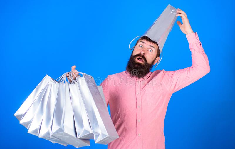 Man with beard and mustache carries shopping bags, blue background. Guy shopping on sales season with discounts. Shopping concept. Hipster on surprised face royalty free stock image