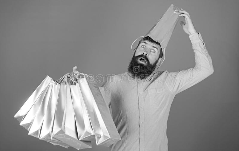 Man with beard and mustache carries shopping bags, blue background. Guy shopping on sales season with discounts. Shopping concept. Hipster on surprised face stock photo