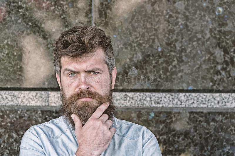 Man with beard and mustache on concentrated face, black marble background. Masculinity concept. Hipster with tousled. Hair touches beard while looking at camera stock photography
