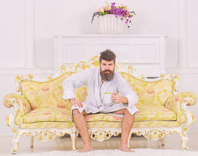 Man with beard and mustache enjoys morning while sitting on luxury sofa. Man on sleepy strict face in bathrobe, drinks. Coffee, in luxury hotel in morning stock photo
