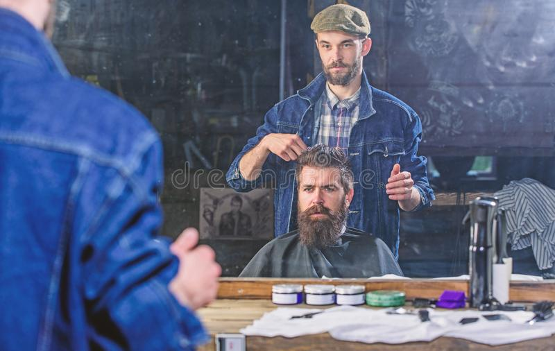 Man with beard and mustache in hairdressers chair in front of mirror background. Hipster client getting hairstyle. Reflexion of barber styling hair of bearded stock image