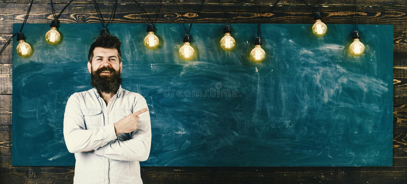 Man with beard and mustache on happy smiling face stand in front of chalkboard. Guy pointing with finger at board. Home royalty free stock photos
