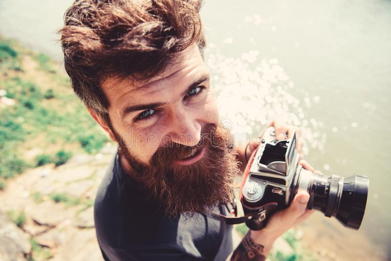 Man with beard and mustache holds camera, outdoor on sunny day, water surface on background. Photographer concept. Hipster on smiling face holds old fashioned royalty free stock images