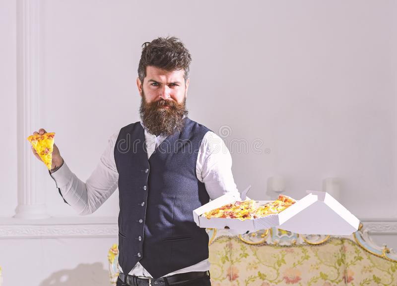 Man with beard and mustache holds delivered box with tasty fresh hot pizza. Macho in classic clothes hungry, on. Man with beard and mustache holds delivered box stock photo