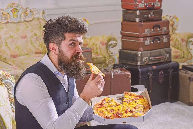 Man with beard and mustache holds delivered box with tasty fresh hot pizza. Macho in classic clothes hungry, on strict. Face, bites slice of pizza, eats royalty free stock image