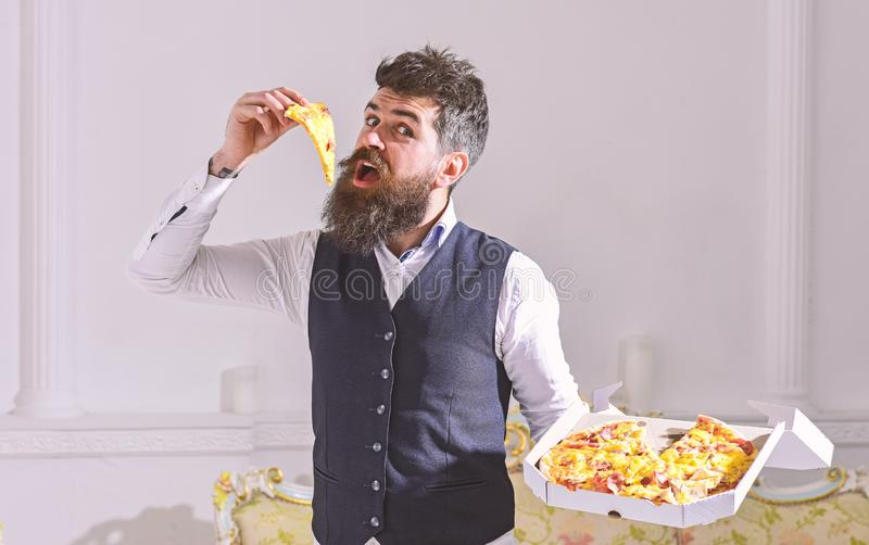 Man with beard and mustache holds delivered box with tasty fresh hot pizza. Pizza delivery concept. Macho in classic. Clothes hungry, on cheerful face, bites stock photos