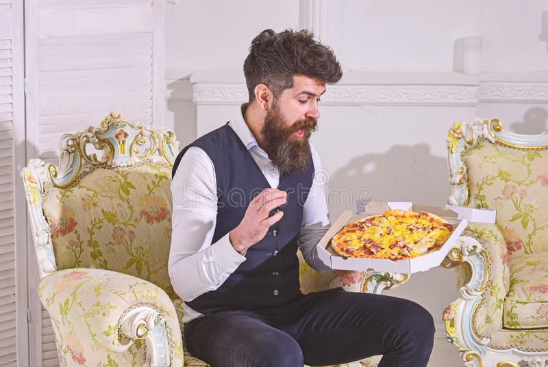 Man with beard and mustache holds delivered box with tasty fresh hot pizza. Pizza delivery concept. Macho in classic. Clothes hungry, on surprised face, going stock image