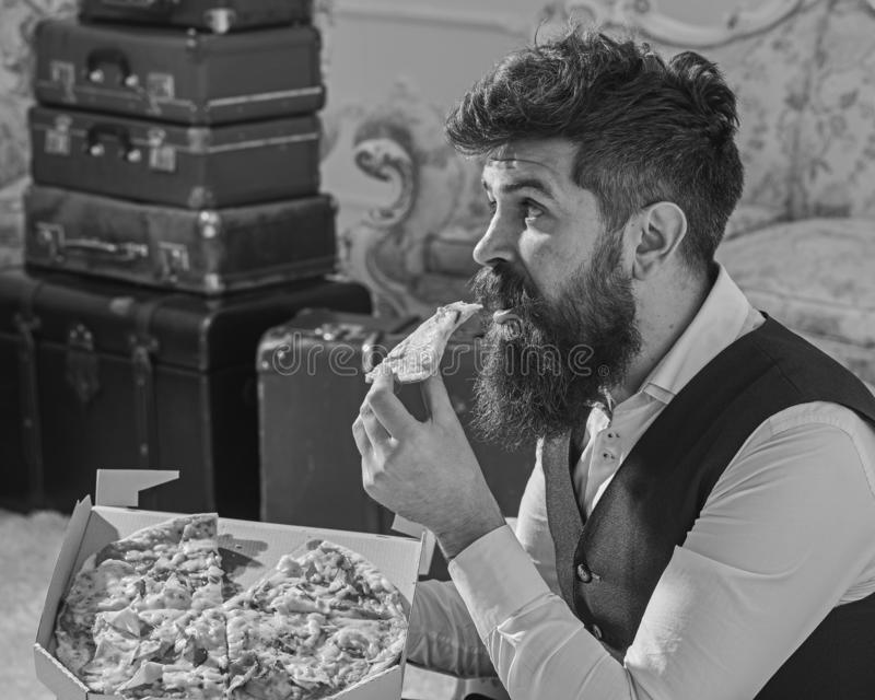 Man with beard and mustache holds delivered box with tasty fresh hot pizza. Pizza delivery concept. Macho in classic. Clothes hungry, on surprised face, bites stock images