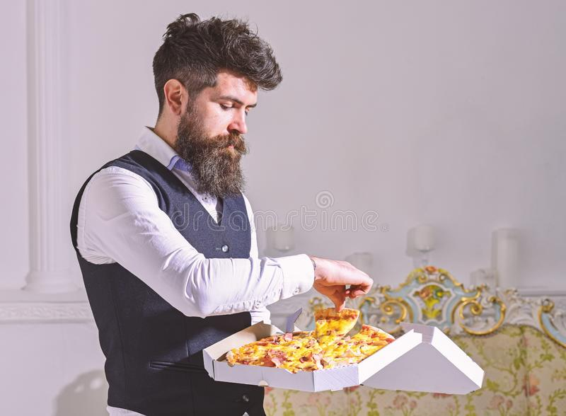 Man with beard and mustache holds delivered box with tasty fresh hot pizza. Pizza delivery concept. Macho in classic. Clothes hungry, on strict face, going to royalty free stock photography