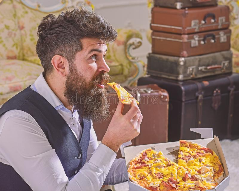 Man with beard and mustache holds delivered box with tasty fresh hot pizza. Pizza delivery concept. Macho in classic. Clothes hungry, on surprised face, bites stock photos