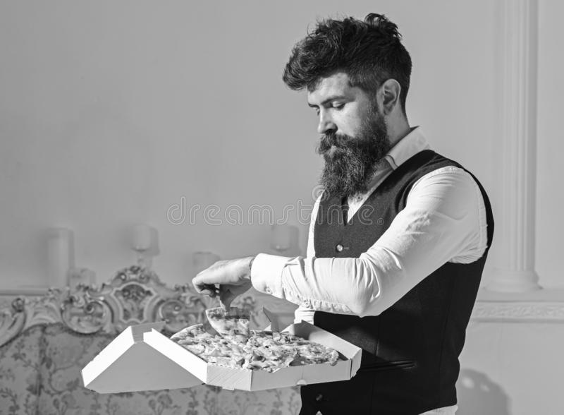 Man with beard and mustache holds delivered box with tasty fresh hot pizza. Pizza delivery concept. Macho in classic. Clothes hungry, on strict face, going to stock photos
