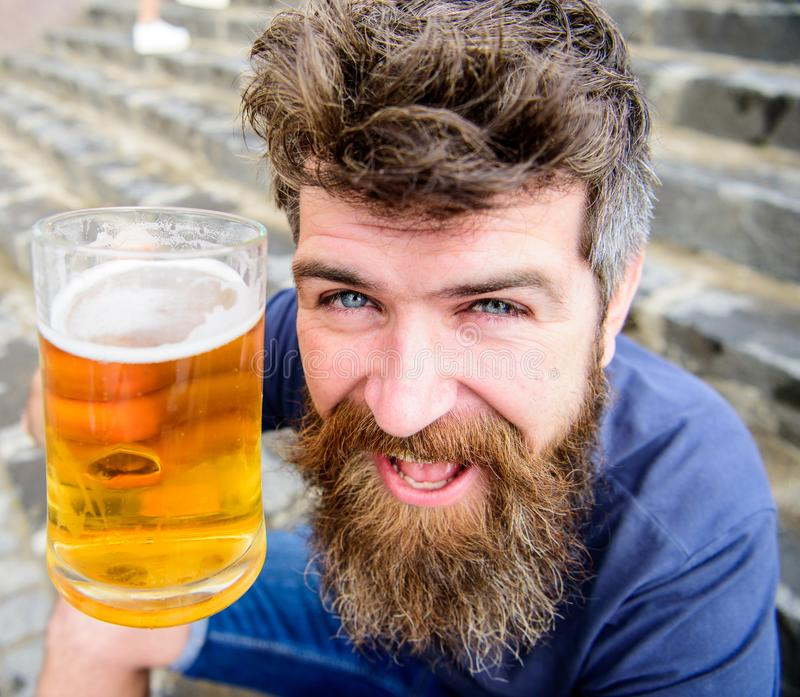 Man with beard and mustache holds glass with beer while sits on stone stairs. Friday relax concept. Hipster on cheerful. Face drinking beer outdoor. Guy having royalty free stock photos