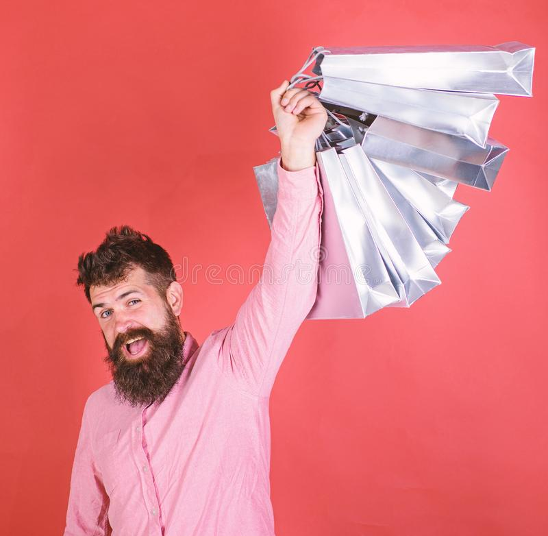 Man with beard and mustache holds shopping bags, red background. Guy shopping on sales season with discounts. Shopping. Concept. Hipster on happy face is royalty free stock photos