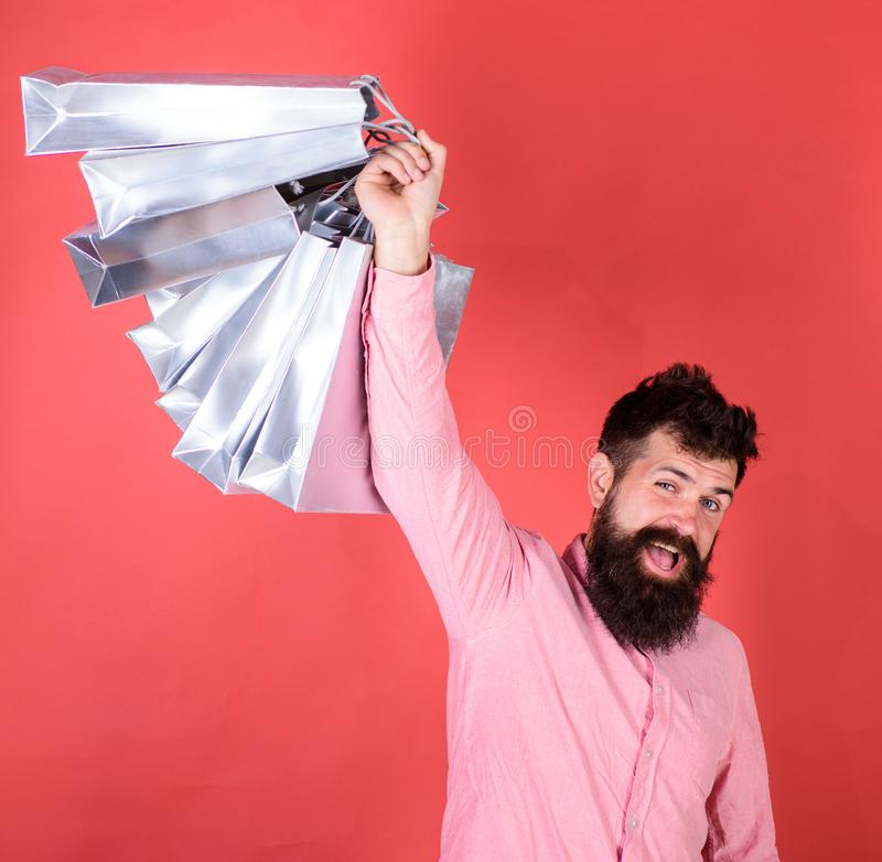 Man with beard and mustache holds shopping bags, red background. Guy shopping on sales season with discounts. Shopping. Concept. Hipster on happy face is royalty free stock photography
