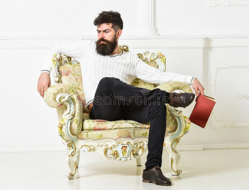Man with beard and mustache sits on armchair, holds book, white wall background. Connoisseur on thoughtful face finished. Reading book. Guy thinking about stock photography