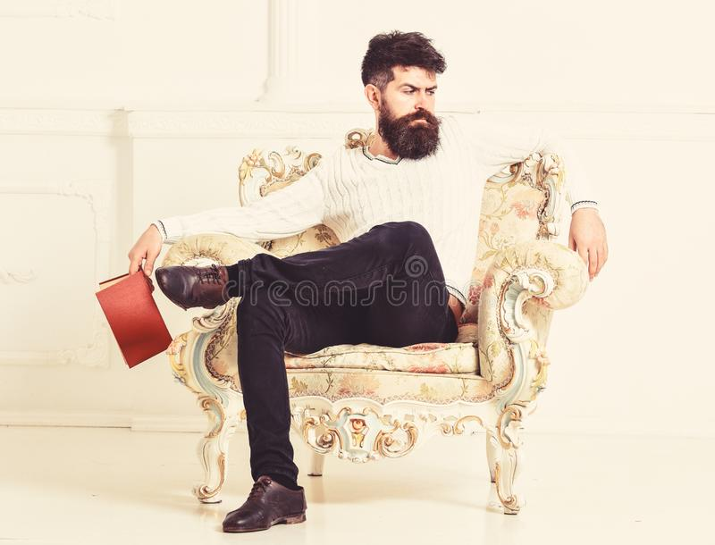 Man with beard and mustache sits on armchair, holds book, white wall background. Connoisseur on thoughtful face finished. Reading book. Guy thinking about royalty free stock image