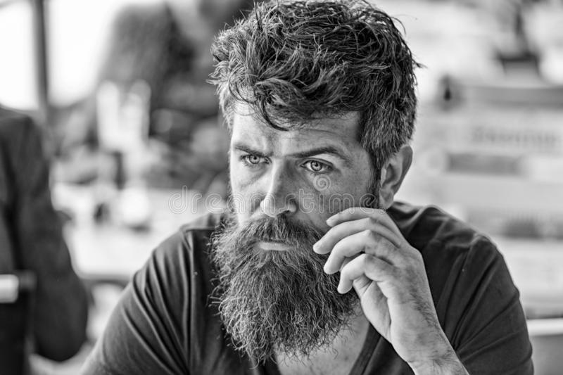 Man with beard and mustache sits outdoor at cafe terrace. Bearded man on calm face looks sad and troubled. Hipster with. Beard going through difficult times stock image
