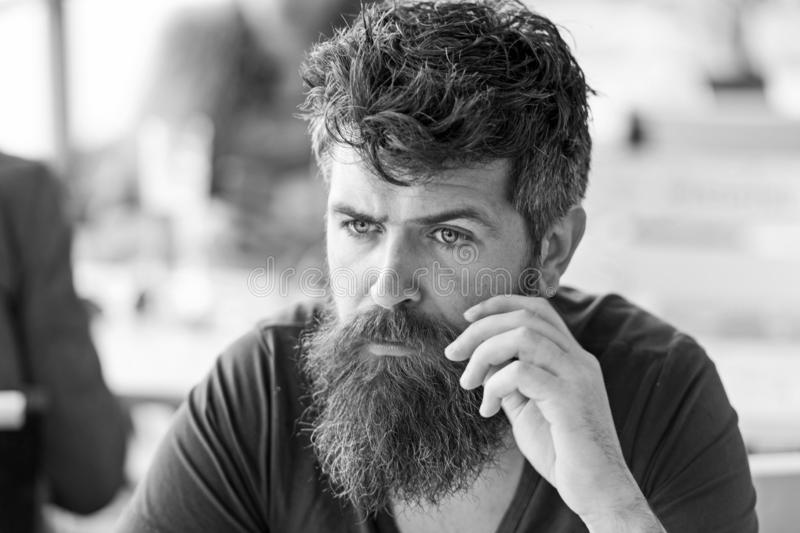 Man with beard and mustache sits outdoor at cafe terrace. Bearded man on concentrated face touches mustache. Hipster. With beard looks thoughtful or troubled royalty free stock images