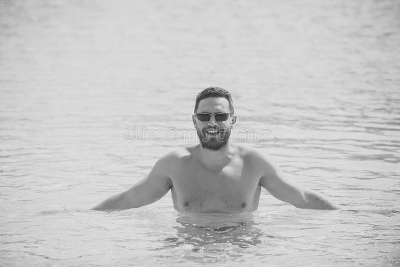 Man standing waist deep in blue sea water royalty free stock image
