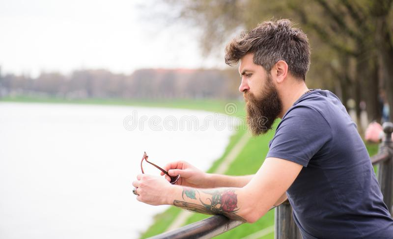 Man with beard and mustache with sunglasses, riverside on background. Hipster on thoughtful face standing at riverside stock photos