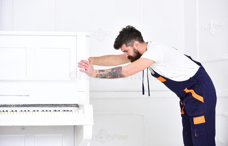 Man with beard and mustache, worker in overalls pushes piano, white background. Delivery service concept. Loader moves stock photography