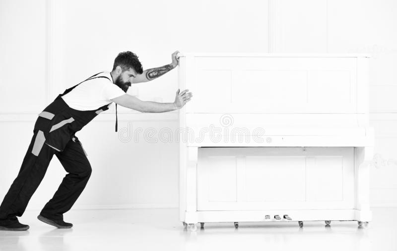 Man with beard and mustache, worker in overalls pushes piano, white background. Loader moves piano instrument. Courier. Delivers furniture in case of move out stock photography