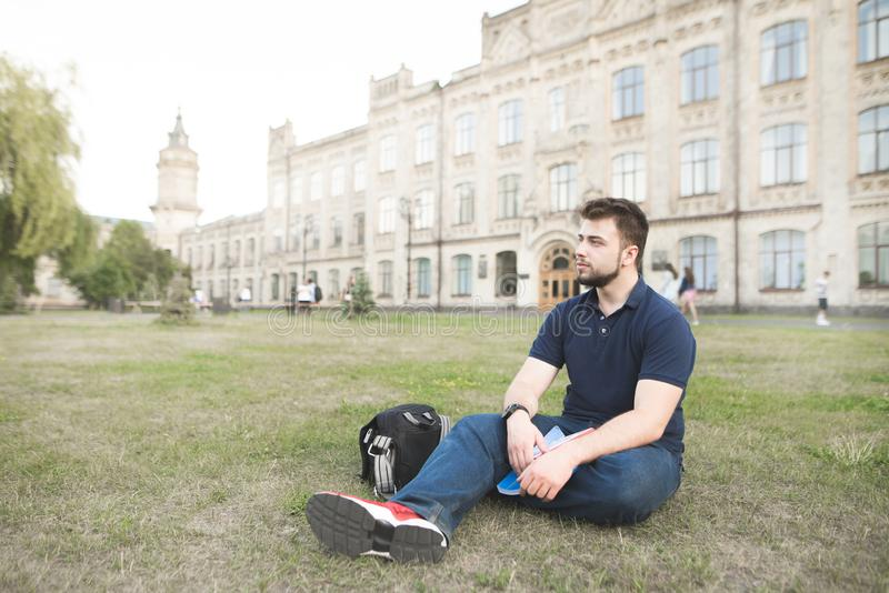 Man with a beard sits on the grass near the university and looks to the side. Student sitting on a lawn at a university campus and resting. Man with a beard sits royalty free stock photo