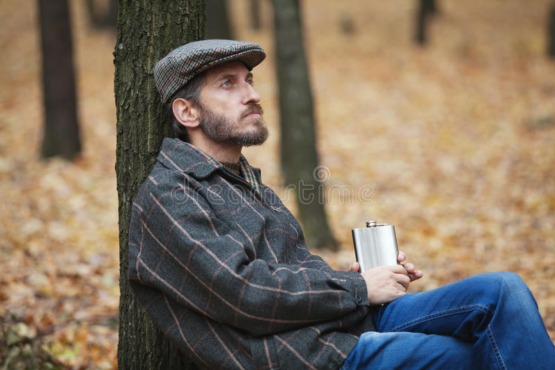 Man with a beard sitting in the autumn forest with a flask in hi. Pensive man with a beard wearing a cap leans back against the tree trunk and holding a royalty free stock photography