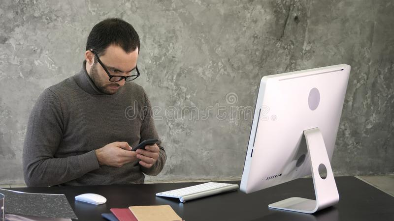 Man with beard, he is sitting at a black table, looking at his smartphone with his computer in front of him. stock image