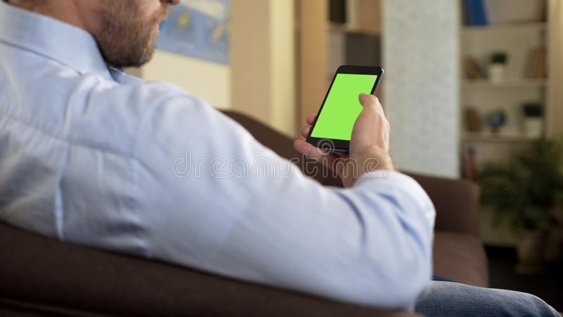 Man with beard sitting on sofa holding green screen smartphone, business app stock photography
