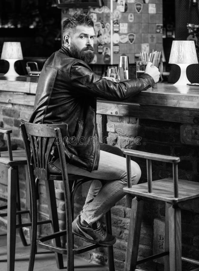 Man with beard spend leisure in dark pub. Brutal hipster relaxing. Weekend lifestyle. Guy bearded man sit at bar counter. In pub. Pub great place to dine drink stock photography
